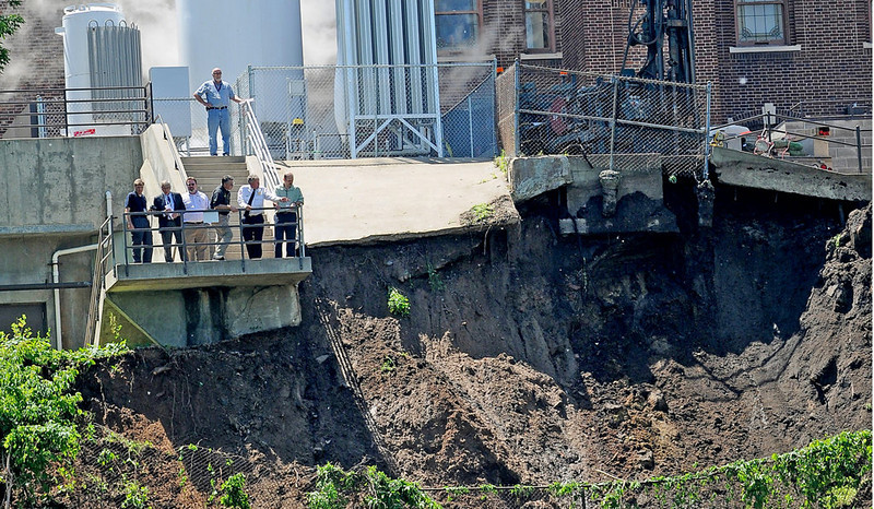 Observers look over a 100-yard-wide section of rain-soaked Mississippi River bluff, which slid onto West River Parkway during Thursday's storms, in Minneapolis on Friday, June 20, 2014. (Pioneer Press: Jean Pieri)