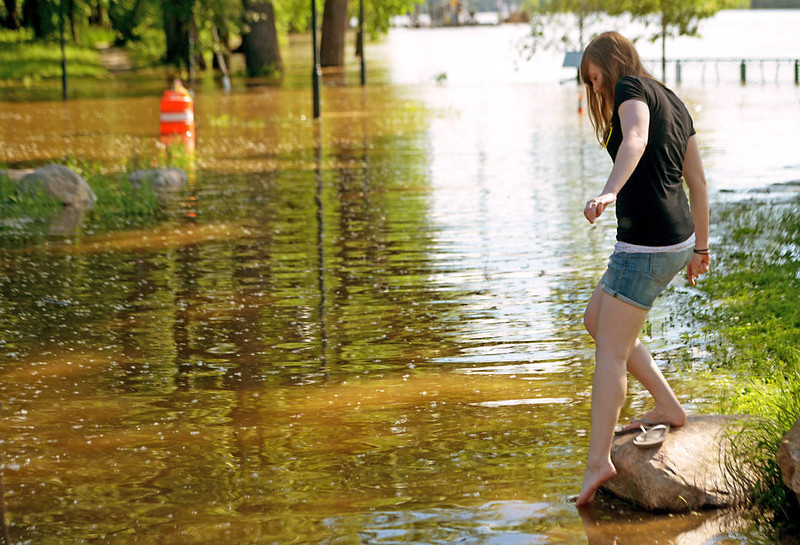 Tessa Lietzau of Mankato dips her toes in the Mississippi River as it floods the low-lying area on the west end of Harriet Island in St. Paul on Friday. (Pioneer Press: John Autey)