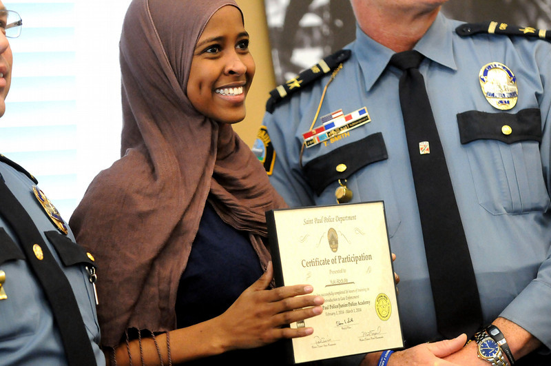 Yuki Abdulle, 19, smiles as she receives her certificate of participation from Chief of Police Thomas Smith, right, and Assistand Chief Todd Axtell, left, during a graduation ceremony on Saturday, March 1, 2014, for the East African Junior Police Academy at the Western District Police Station in St. Paul. (Pioneer Press: Sherri LaRose-Chiglo)