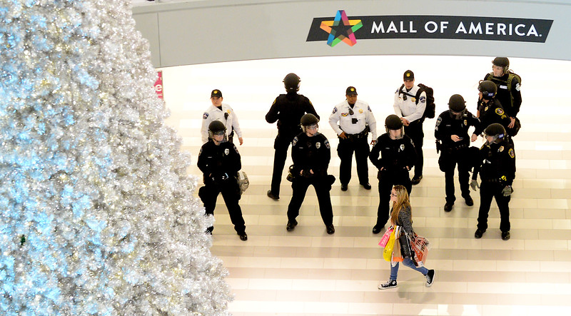 A shopper walks past a group of police in the rotunda area during the Black Lives Matter demonstration at the Mall of America. (Pioneer Press: John Autey)