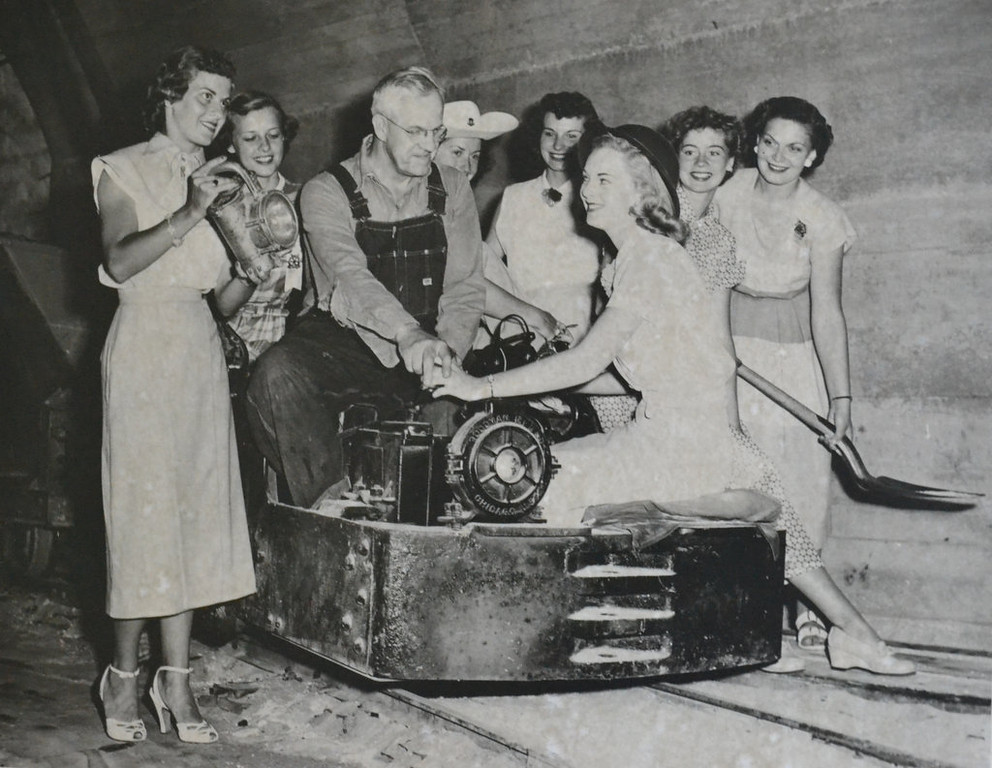 "Description of . Writes STEVE KELLER: ""Here is a photo taken by the KSTP news team on December 30, 1954, of my grandfather, A.P. Mitchell, with models on a photo shoot of the silica mines at Ford Motor Company in St. Paul. He worked there for close to 30 years. After the mines closed, he worked in the paint department. Please note the miner's lantern, and he is seated on the engine. The piece was aired on Channel 5 by Bill Ingram, titled 'Behind Private Doors.' Question is this: Do any of the readers out there recognize any of the models, and are they still around? I very much would like to ask them about that day — another small part of St. Paul history gone forever. Thanks for your time.""    BULLETIN BOARD QUIBBLES (?): It's not gone forever! It's still right here, in the St. Paul Pioneer Press, on the 29th of June in 2013. Photographs and newsprint make the past present — not to mention permanent."