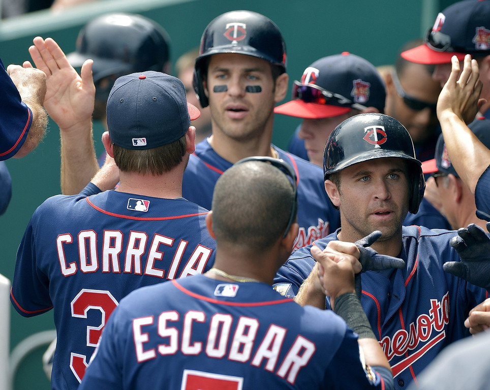 . The Minnesota Twins\' Brian Dozier (2) and Joe Mauer (7) are greeted in the dugout after both scored in the first inning. (John Sleezer/Kansas City Star/MCT)