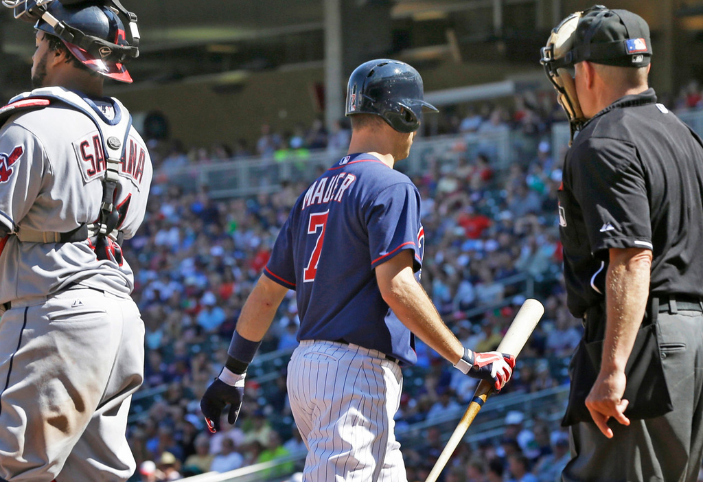 . Minnesota\'s Joe Mauer, center, returns to the dugout after striking out in the ninth inning against the Indians. Cleveland catcher Carlos Santana is at left; home plate ump Jerry Meals is at right.  (AP Photo/Jim Mone)