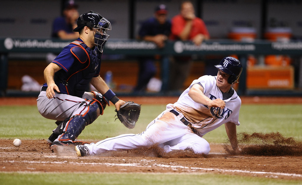 . Tampa Bay Rays\' Wil Myers, right, scores in front of Minnesota Twins catcher Joe Mauer on a sacrifice fly by Yunel Escobar during the eighth inning. (AP Photo/Brian Blanco)