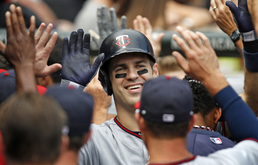 . Minnesota\'s Joe Mauer celebrates in the dugout after hitting a two-run home run against the White Sox during the fifth inning, his ninth homer of the season. The Twins beat the White Sox, 5-2, at U.S. Cellular Field in Chicago on Sunday August 11, 2013.  (AP Photo/Andrew A. Nelles)