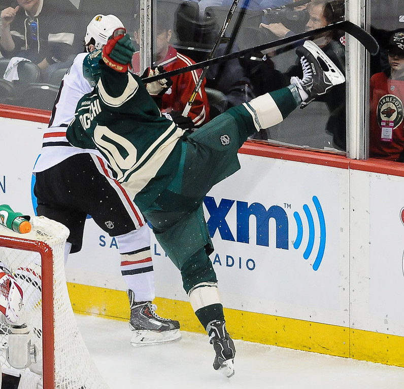. Minnesota\'s Devin Setoguchi is knocked off his feet from a hard hit from Chicago defenseman Nick Leddy during the overtime period. (Pioneer Press: Ben Garvin)