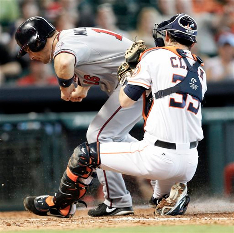 . Minnesota Twins\' Josh Willingham  is tagged out by Houston Astros catcher Cody Clark (39) as he tries to score in the fifth inning. (AP Photo/Bob Levey)