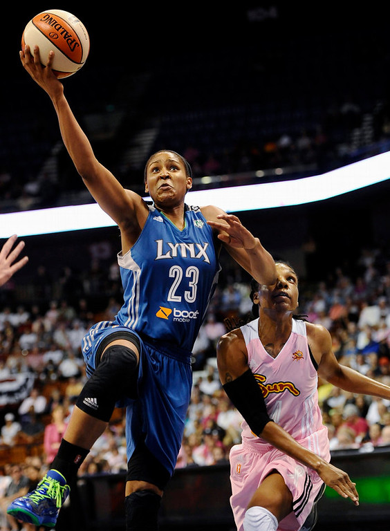 . Minnesota Lynx\'s Maya Moore, left, goes up for a shot while guarded by Connecticut Sun\'s Tan White during the first half.  (AP Photo/Jessica Hill)