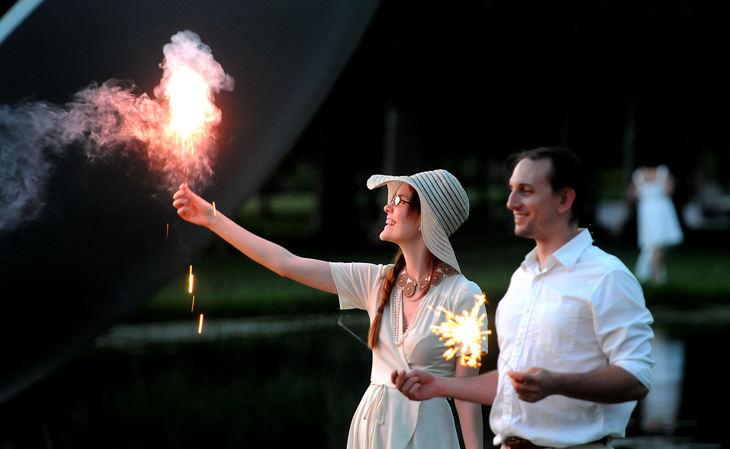 . Content and well-fed diners Kat Reaney, left, and Aston Troia wave sparklers, signaling the conclusion of their first Dinner in White. (Pioneer Press: Sherri LaRose-Chiglo)