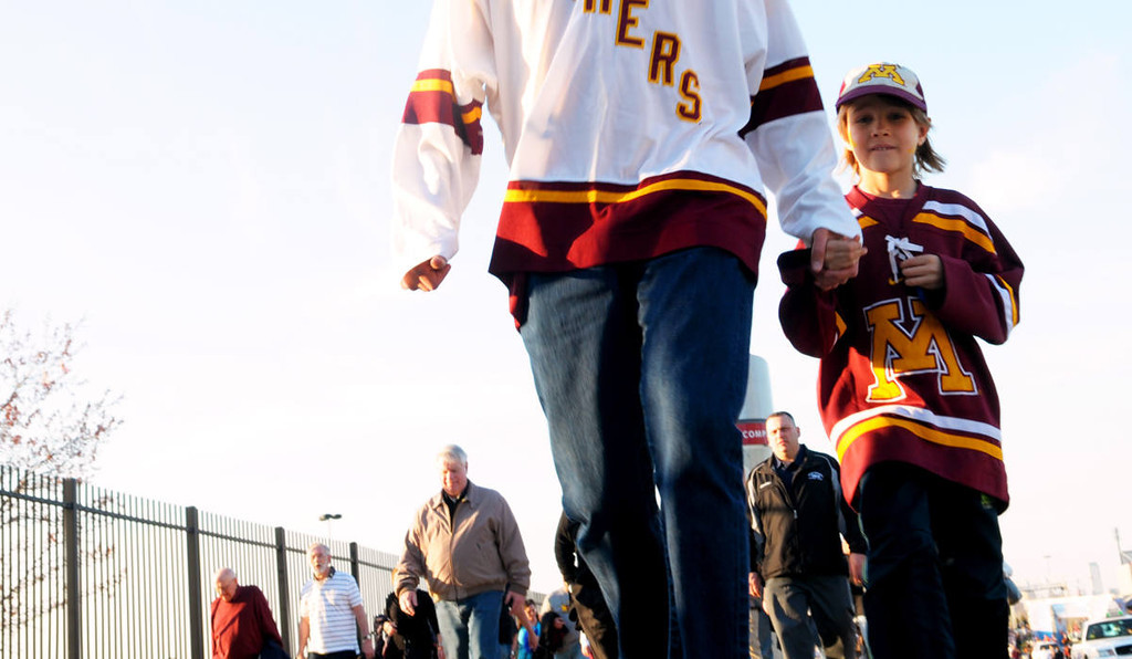 . Calum Axelsm, seven years-old, holds his dad hand, Davi, as the St. Paul pair walk into the Wells Fargo Center prior to the start of the NCAA Frozen Four Championship Game Philadelphia, Saturday, April 12, 2014.  (Pioneer Press: John Autey)