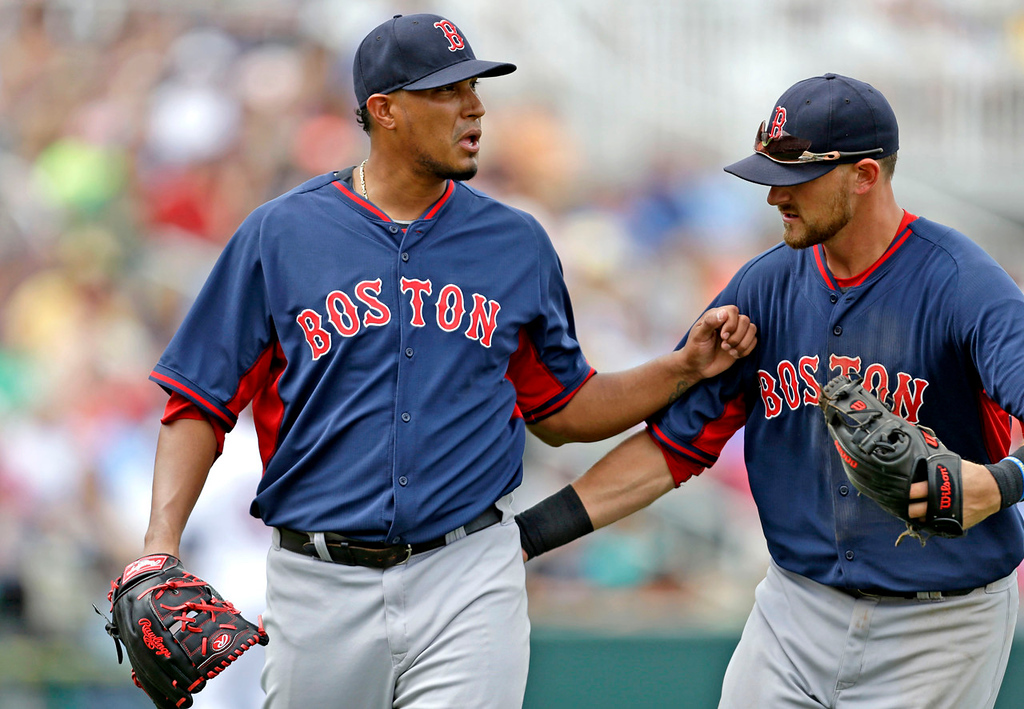 . Red Sox third baseman Will Middlebrooks, right, pats starter Felix Doubront as he walks off the mound at the end of the fourth inning. Doubront scattered seven Twins hits over five scoreless innings. (AP Photo/Gerald Herbert)