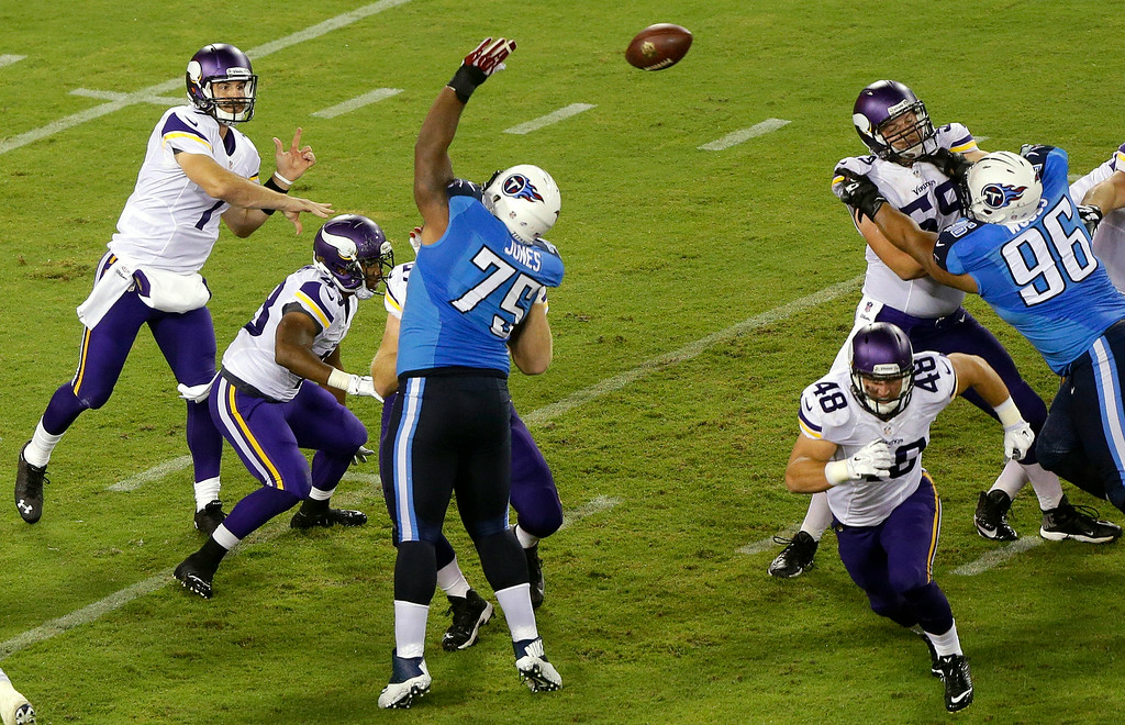 . Minnesota Vikings quarterback Christian Ponder, top left, passes over the reach of Tennessee Titans defensive tackle DaQuan Jones (75) in the third quarter. (AP Photo/Wade Payne)