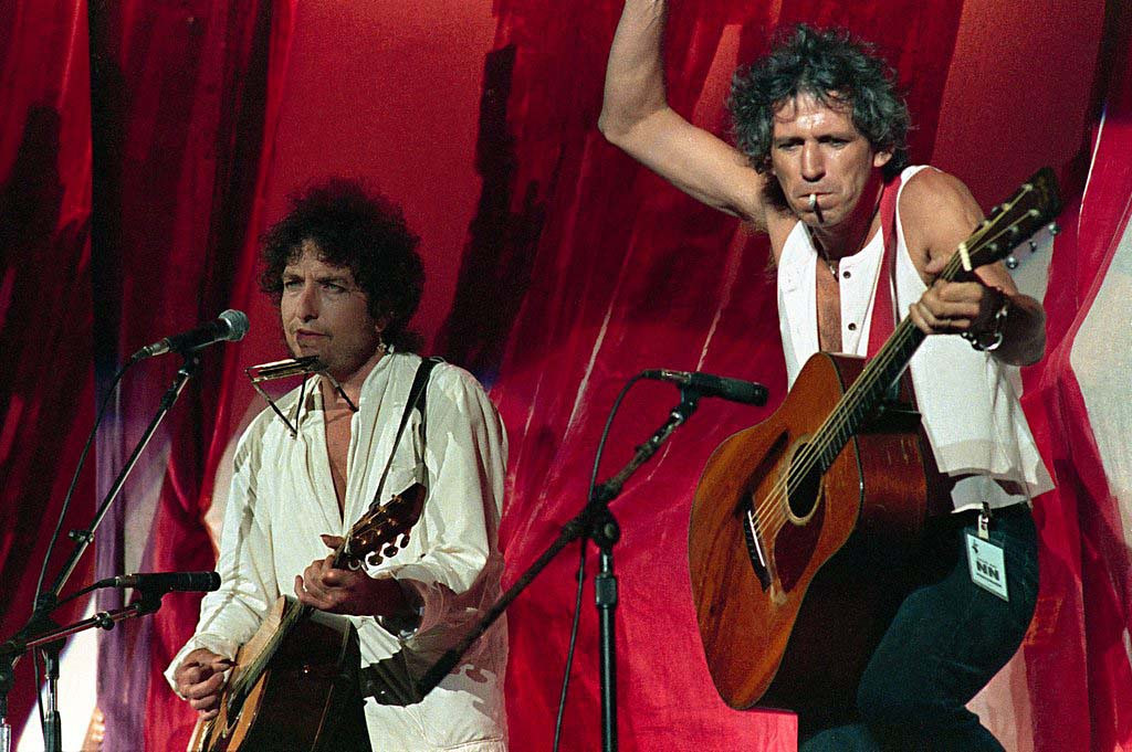 . American singer-songwriter Bob Dylan, left, is joined onstage by Rolling Stones guitarist Keith Richards during Live Aid famine relief concert at JFK Stadium in Philadelphia on July 13,1985. (AP Photo/Amy Sancetta)