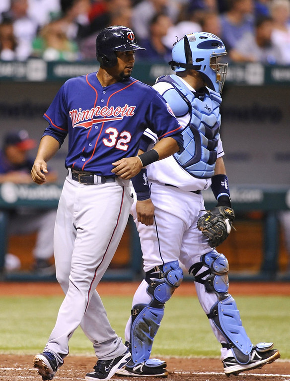 . Tampa Bay Rays catcher Jose Molina, right, watches as Minnesota Twins\' Aaron Hicks scores off of Brian Dozier\' double during the third inning.(AP Photo/Brian Blanco)