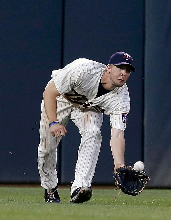. Minnesota Twins left fielder Clete Thomas assumes a low profile to catch a shallow fly ball off the bat of Cleveland Indians\' Michael Bourn for an out in the eighth inning. (AP Photo/Jim Mone)