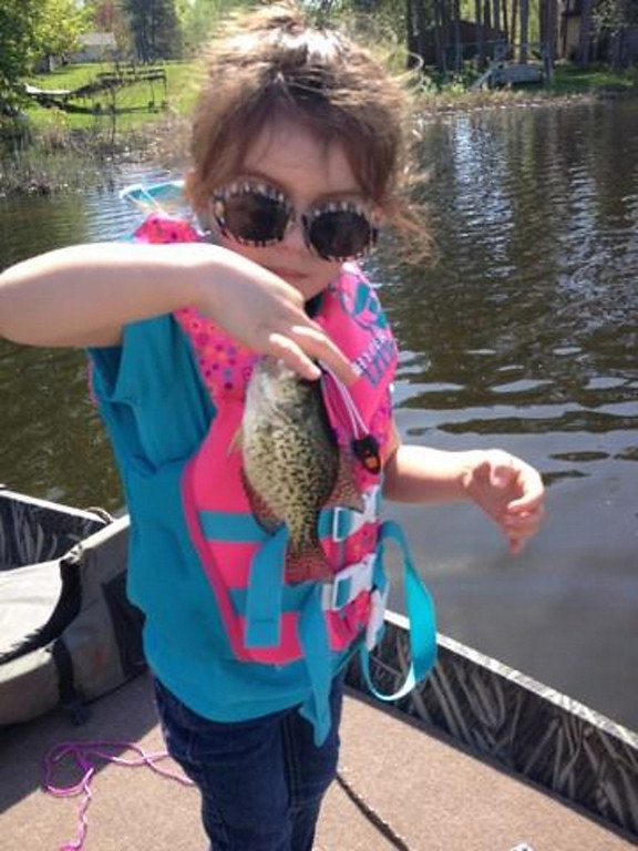 """. Gigi Soto Valento, 4, of South St. Paul, caught and released this crappie while fishing near Scandia with her dad Jose\' and grandpa Porky May 25.  It was her first time fishing. \""""This is so fun!\"""" she said. (Photo courtesy Lynne Scharffbillig)"""