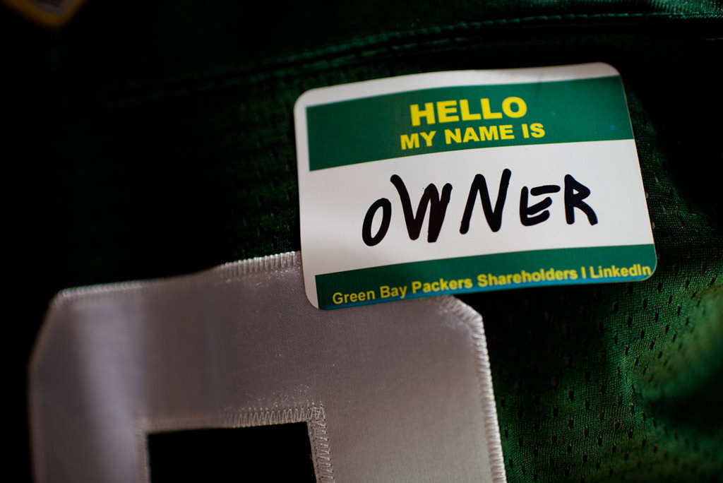 ". Jim Spath of Wisconsin Rapids, Wis.  wears an ""owner\"" name tag during the Packers annual shareholders meeting at Lambeau Field. (AP Photo/The Green Bay Press-Gazette, Lukas Keapproth)"