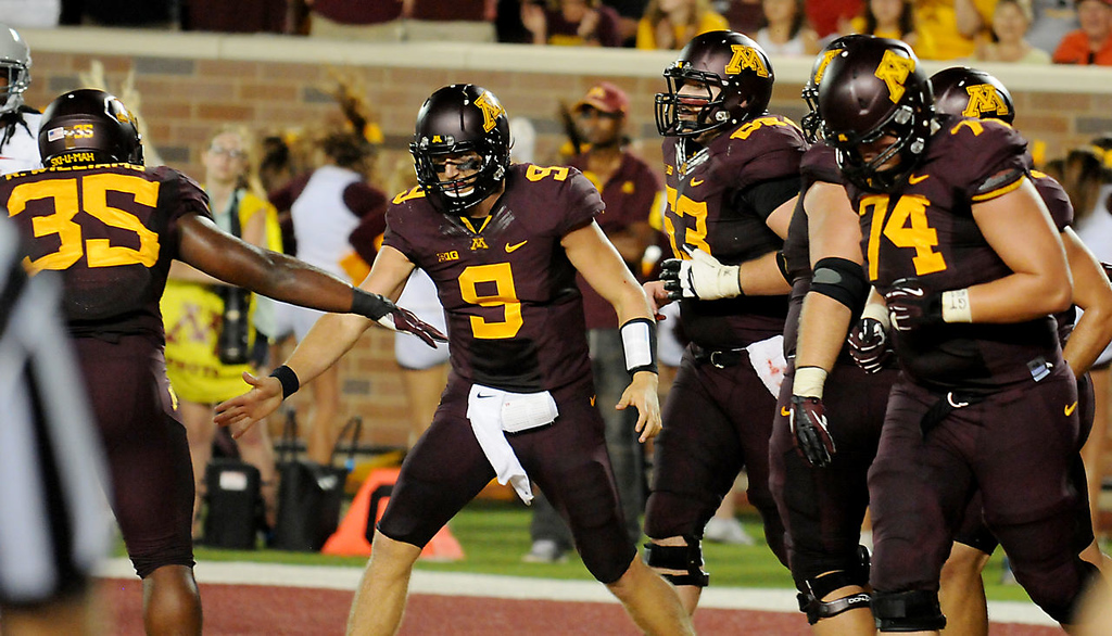 . Minnesota quarterback Philip Nelson is congratulated by running back Rodrick Williams Jr., left, after Nelson scored on a five-yard run during the first quarter. (Pioneer Press: John Autey)