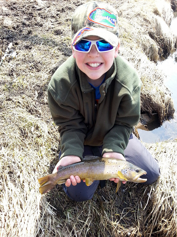 """. Brock Anderson, 10, of Rochester caught this brown trout on the last cast of the day April 6, while fishing with his father Dave in southern Minnesota. \""""Brock threw downstream towards a downed tree in the water when this 19-inch trout appeared,\"""" Dad reports.  \""""He played it well, and I helped him land it, take a few photos, and back into the creek it went.\""""  (Photo courtesy of Dave Anderson)"""