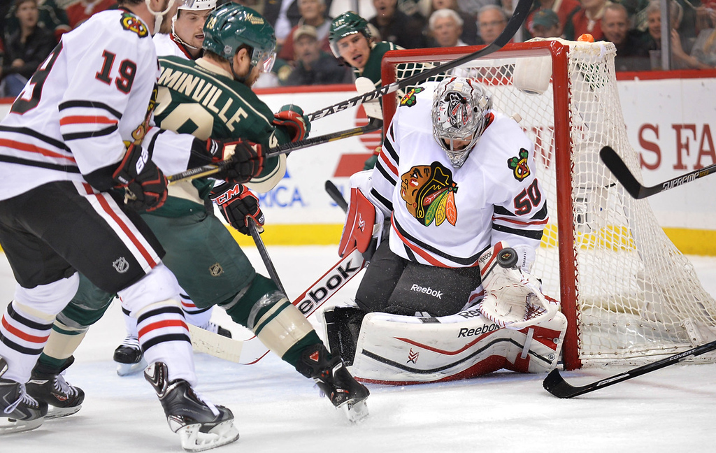 . Blackhawks goalie Corey Crawford makes a glove save on a wrister from Minnesota\'s Jason Pominville during the first period. At left is Chicago\'s Jonathan Toews.  (Pioneer Press: Ben Garvin)