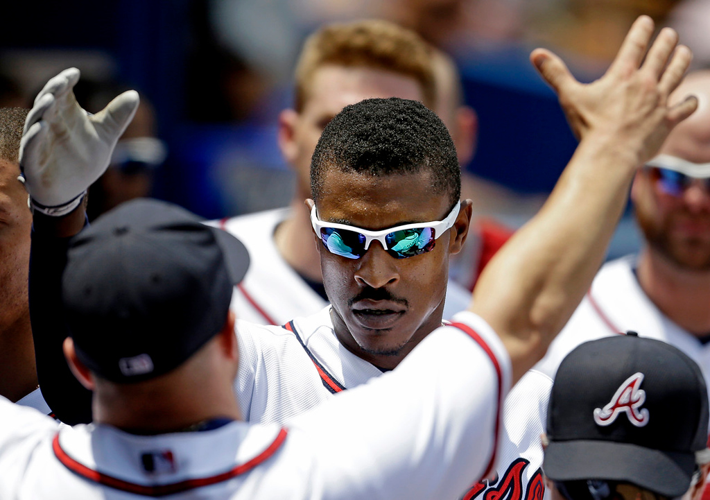 . Atlanta\'s B.J. Upton, center, is embraced by teammate Reed Johnson after leading off the fourth inning with a solo home run against the Twins. (AP Photo/David Goldman)
