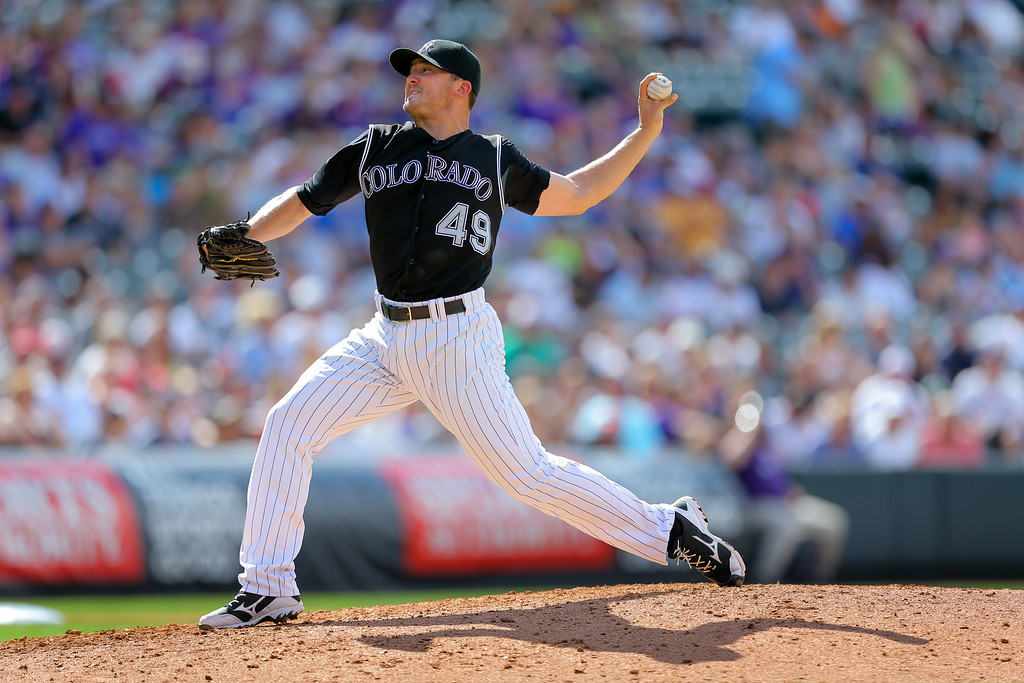 . Relief pitcher Rex Brothers #49 of the Colorado Rockies delivers to home plate during the seventh inning against the Minnesota Twins at Coors Field on July 13, 2014 in Denver, Colorado. The Twins defeated the Rockies 13-5. (Photo by Justin Edmonds/Getty Images)