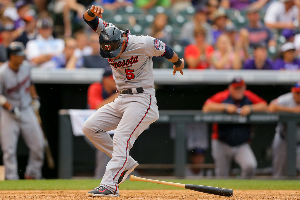 . Eduardo Escobar #5 of the Minnesota Twins trips on a bat as he scores during the ninth inning against the Colorado Rockies at Coors Field on July 13, 2014 in Denver, Colorado.  (Photo by Justin Edmonds/Getty Images)