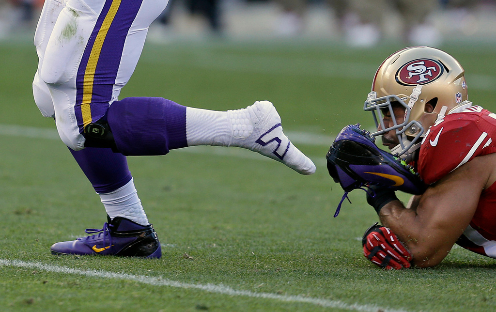 . Vikings running back Toby Gerhart loses his shoe as he runs past 49ers linebacker Michael Wilhoite during the second quarter. (AP Photo/Ben Margot)
