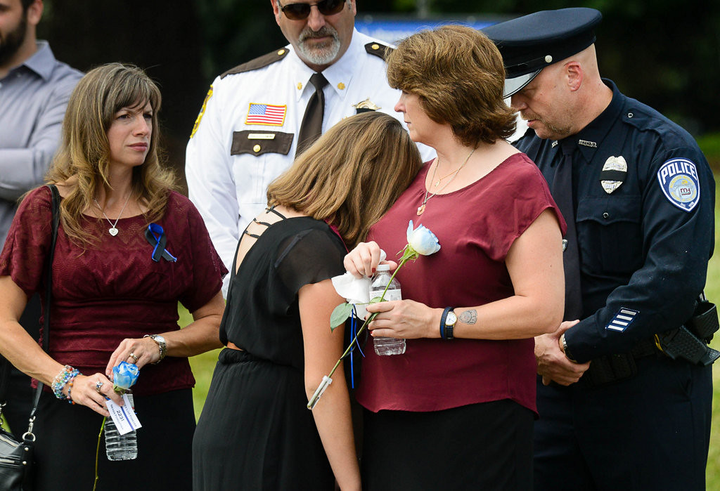 . Amy Patrick rests on her mother Michelle\'s shoulder as they watch the procession of hundreds of police cars. (Pioneer Press: Ben Garvin)