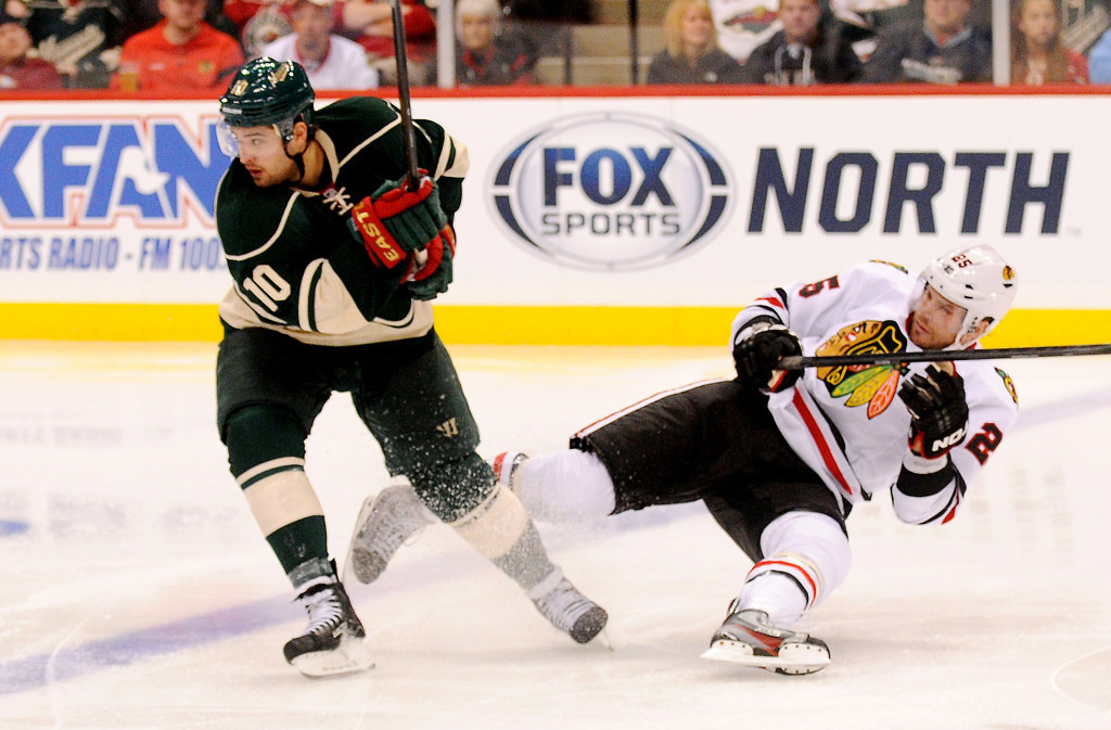 . Chicago left wing Viktor Stalberg, right, hits the ice after skating into Minnesota right wing Devin Setoguchi during the overtime period. (Pioneer Press: John Autey)