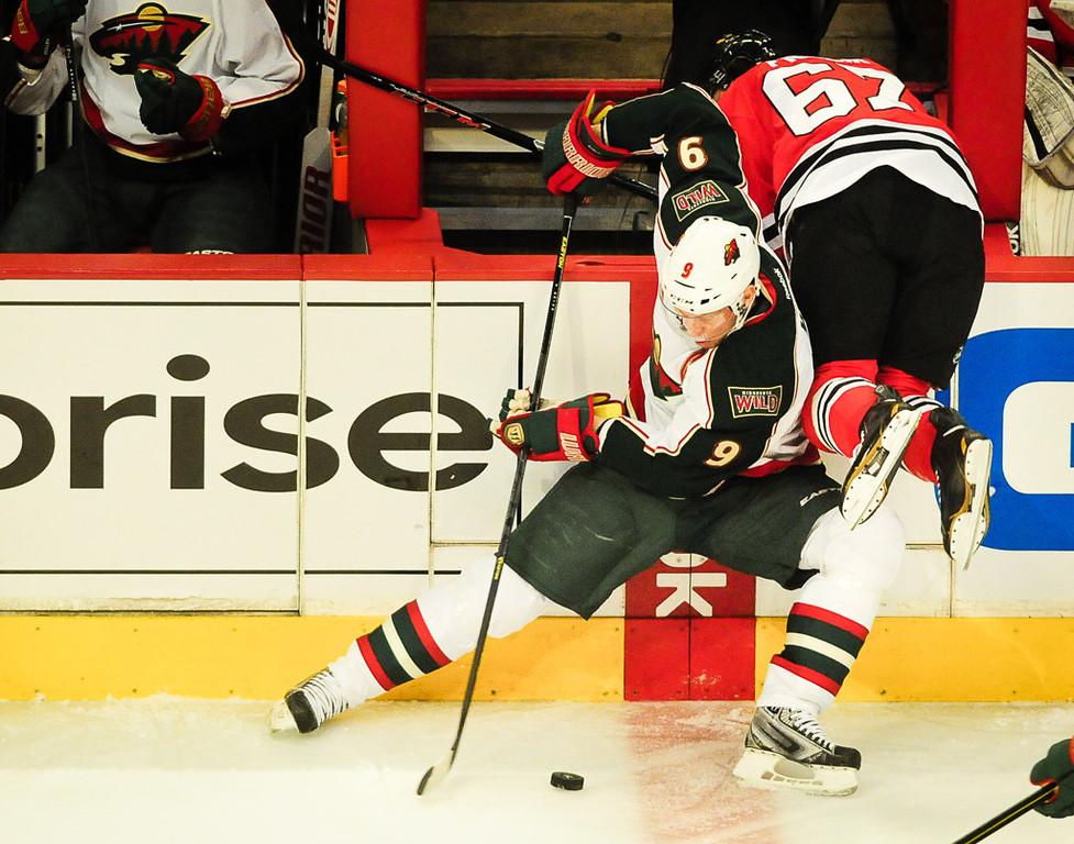 . Wild center Mikko Koivu knocks Blackhawks center Michael Frolik over the boards in the first period.   (Pioneer Press: Ben Garvin)