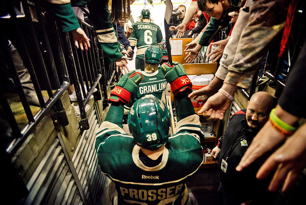 . From bottom, Minnesota Wild defenseman Nate Prosser, center Mikael Granlund and defenseman Marco Scandella head out onto the ice for pregame warmups. (Pioneer Press: Ben Garvin)