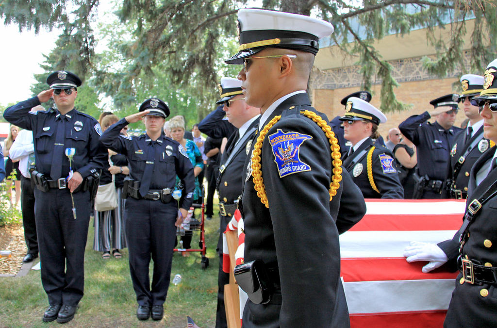 . Mendota Heights police officers salute as officer Scott Patrick\'s casket is carried out of St. Stephen\'s Lutheran Church following his service in West St. Paul on Wednesday. (Minnesota Department of Public Safety Pool Photo: Jen Longaecker)