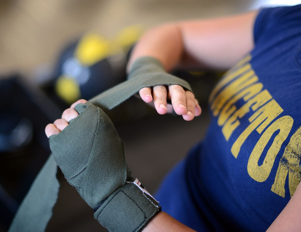 """. Hudson, Wisconsin resident Anne Reuther wraps her hands prior to class at Title Boxing Club. \""""It\'s extremely intense,\"""" she said of the workout. \""""You want to keep coming back.\"""" (Pioneer Press: Chris Polydoroff)"""