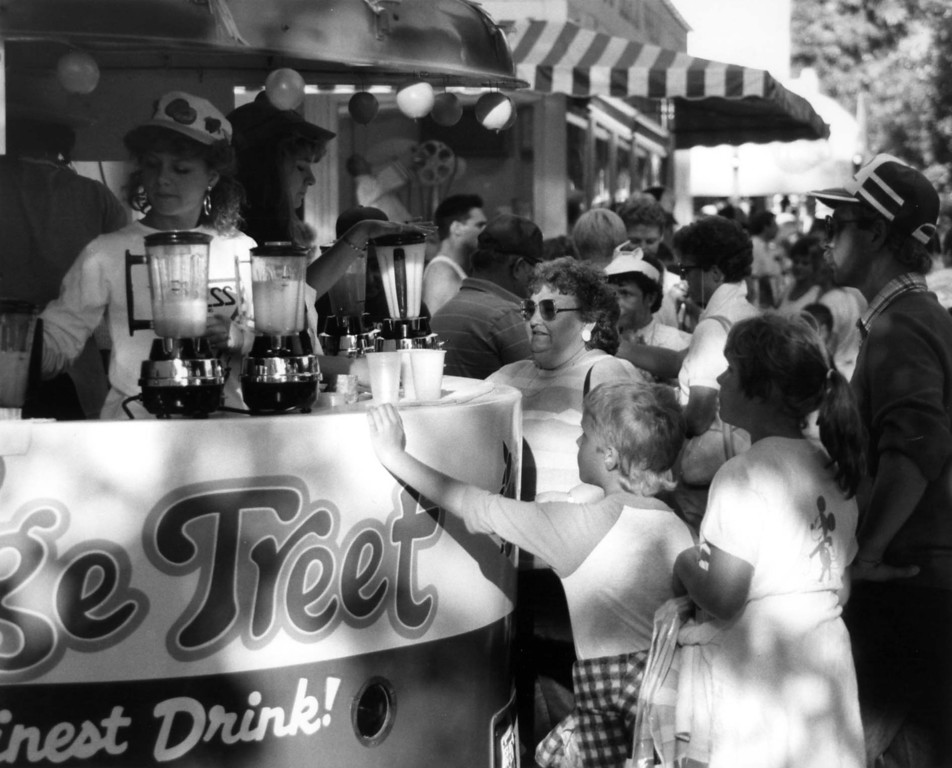 . People surround outside food vendor booths at the 1987 Minnesota State Fair. Orange Treet booth is in the foreground. Photo courtesy of the Minnesota State Fair.