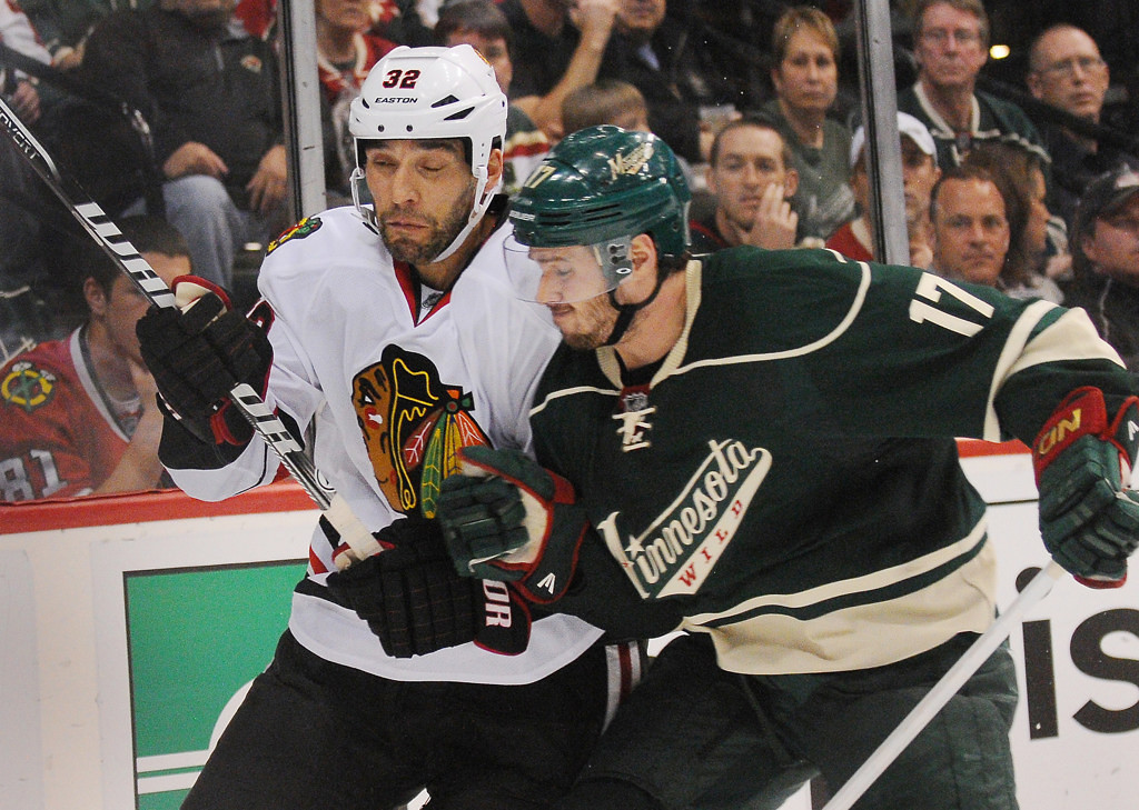 . Minnesota left wing Torrey Mitchell, right, checks Chicago defenseman Michal Rozsival into the boards behind the Blackhawks goal in the second period. (Pioneer Press: John Autey)