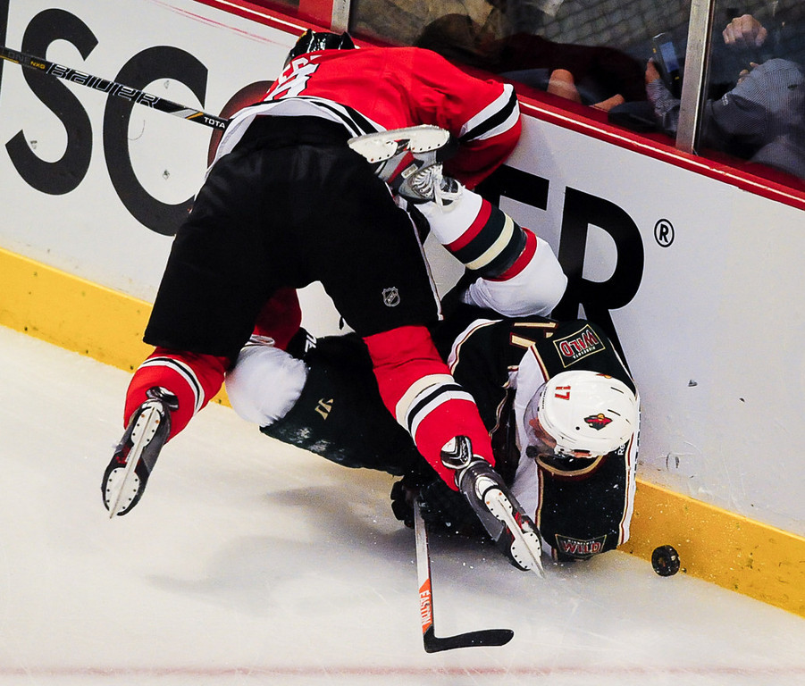 . Minnesota Wild left wing Torrey Mitchell falls to ice as he\'s checked by Chicago Blackhawks defenseman Nick Leddy in the first period. (Pioneer Press: Ben Garvin)