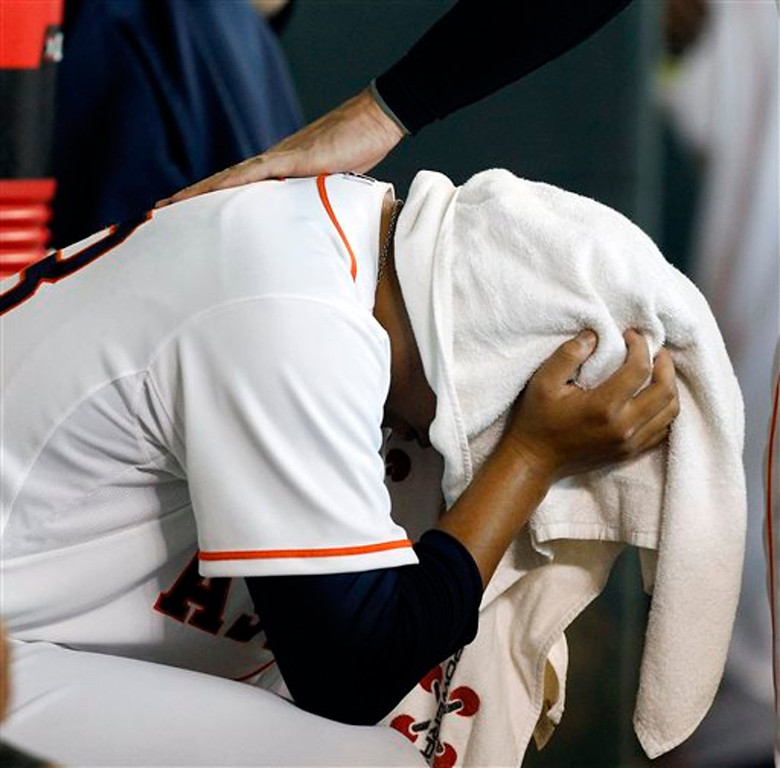 . Houston Astros relief pitcher Chia-Jen Lo buries his head in a towel after giving up a grand slam home run to Minnesota Twins\' Chris Colabello (55) in the ninth inning. The Twins won 10-6. (AP Photo/Bob Levey)
