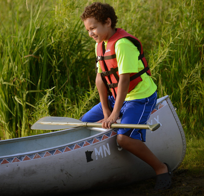 ". A young participant sits on the end of a canoe to stabilize it while his mom takes her seat during the ""I Can Paddle\"" program at Fort Snelling State Park.  (Pioneer Press: Chris Polydoroff)"