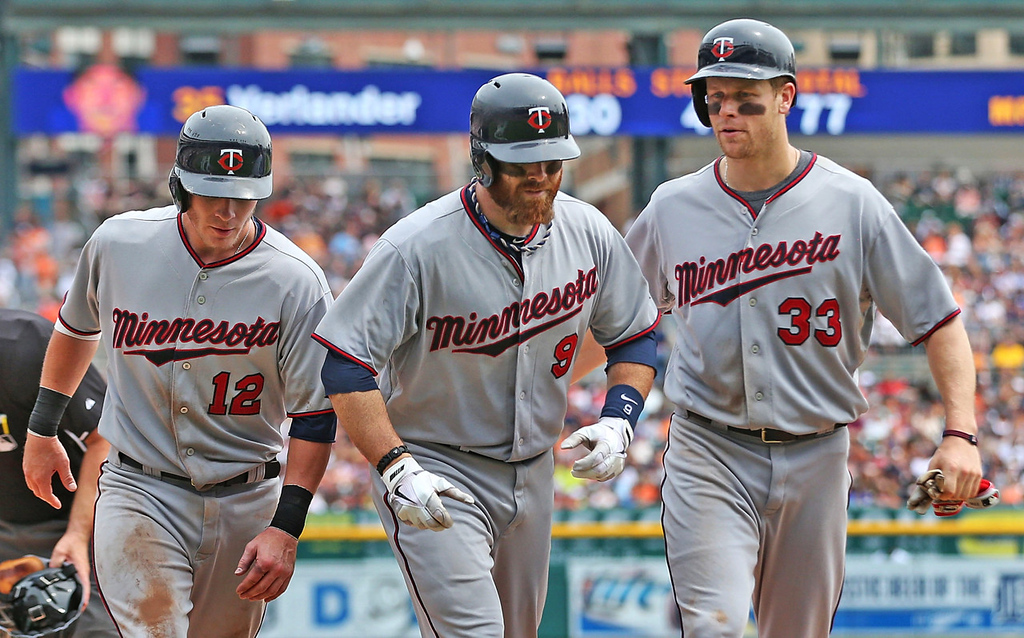 . Minnesota\'s Ryan Doumit, center, heads back to the dugout with Chris Herrmann, left and Justin Morneau, both of whom scored on Doumit\'s three-run homer against the Tigers in the fifth inning.  (Photo by Leon Halip/Getty Images)