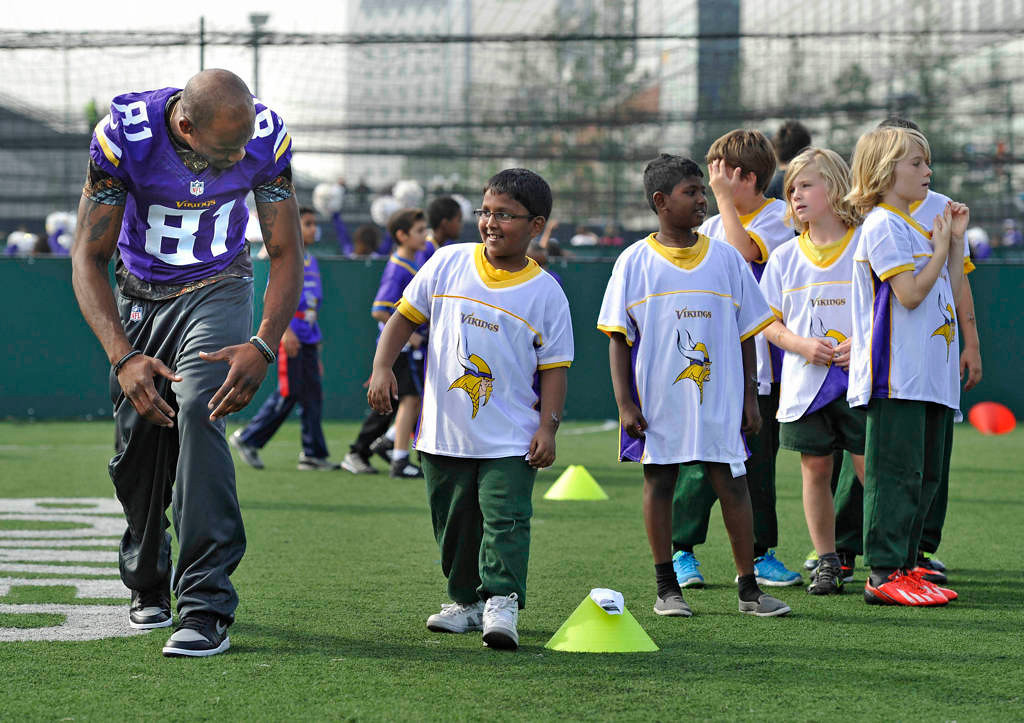 . Minnesota Vikings Jerome Simpson, left, participates in a football clinic at Wembley Stadium in London on Tuesday, Sept. 24, 2014. Vikings players and cheerleaders held a football and cheerleading coaching clinic with London children. (NFL: Sean Ryan)