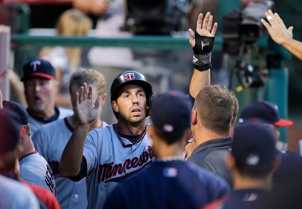 . Minnesota Twins\' Chris Colabello, center, is greeted by teammates after he scored on a double by Clete Thomas in the second inning. (AP Photo/Jae C. Hong)
