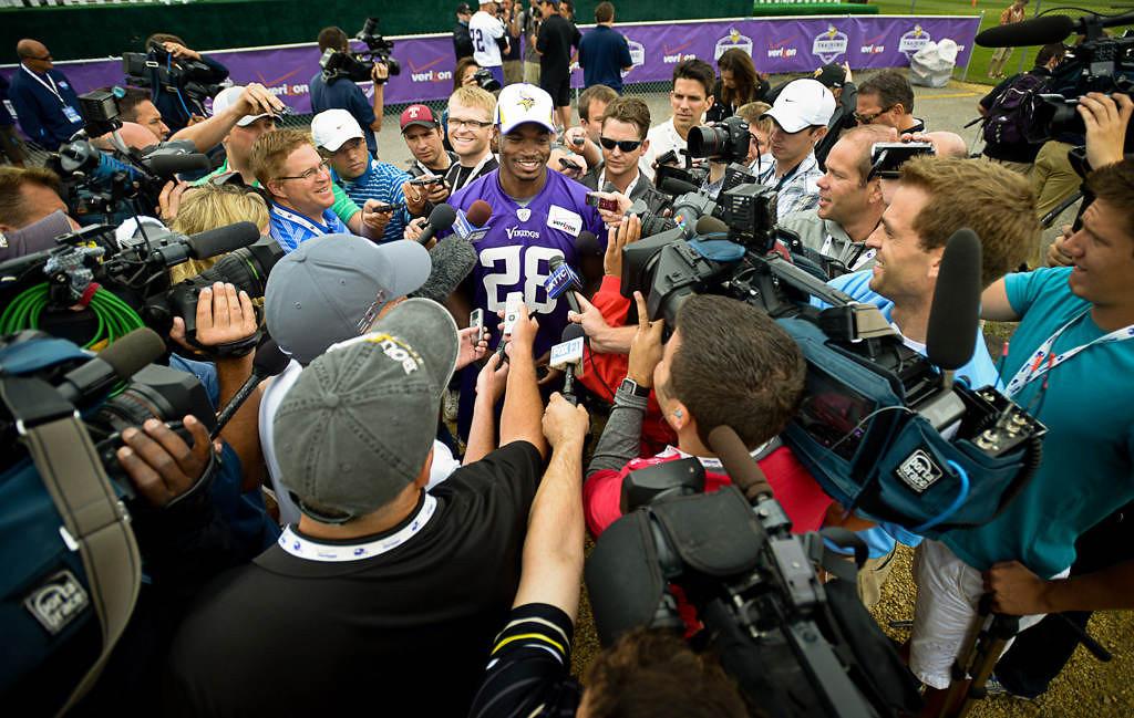 . Vikings running back Adrian Peterson is swarmed by media at Friday\'s camp. (Pioneer Press: Ben Garvin)