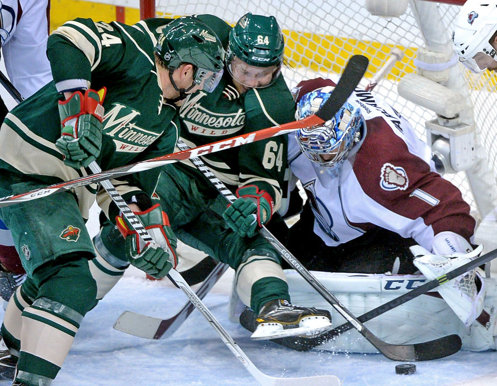 . Minnesota\'s Mikael Granlund, center, falls into Avalanche goaltender Semyon Varlamov as teammate Matt Cooke, left, leans in during the first period. (Pioneer Press: Sherri LaRose-Chiglo)