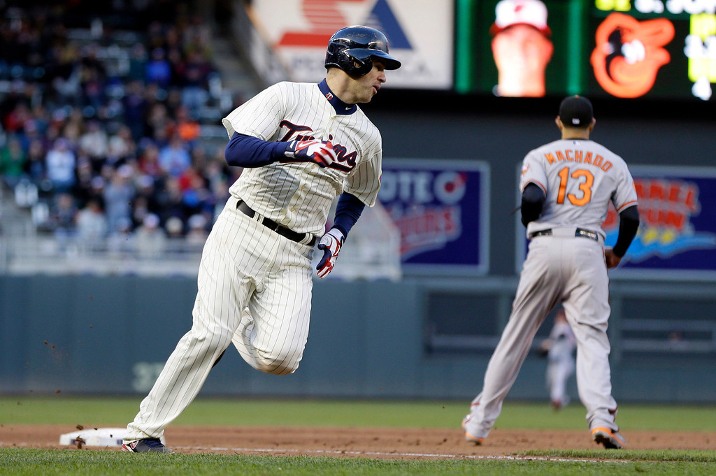 . Minnesota Twins\' Joe Mauer, left, rounds third on his way home to score on a two-run single by Justin Morneau off Baltimore Orioles pitcher Steve Johnson in the fourth inning. (AP Photo/Jim Mone)