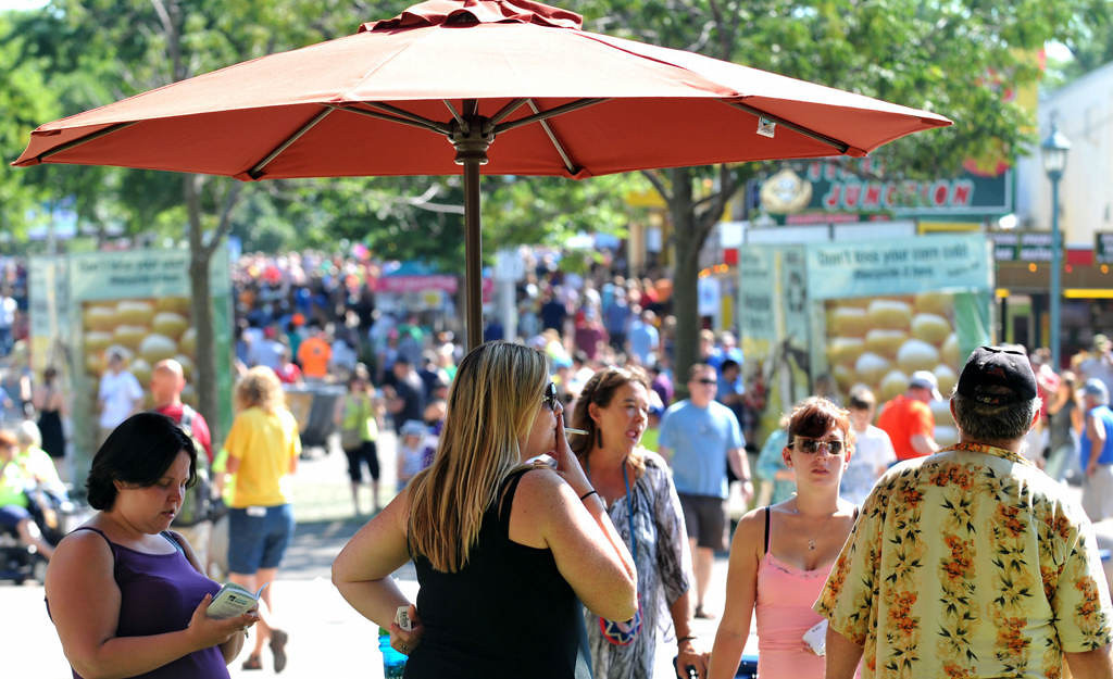 . Smokers gather in the shade of an umbrella at a designated smoking area on Dan Patch Avenue, southeast of the Grandstand at the State Fairgrounds. (Pioneer Press: John Doman)