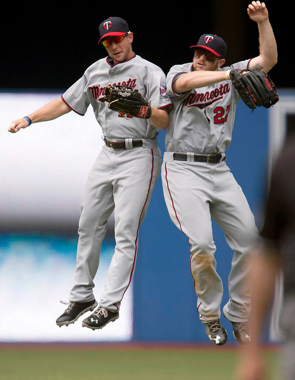. Minnesota Twins\' Clete Thomas, left, and Chris Parmelee celebrate after the Twins defeated the Toronto Blue Jays 6-0 on Saturday, July 6, 2013, in Toronto. (AP Photo/The Canadian Press, Frank Gunn)