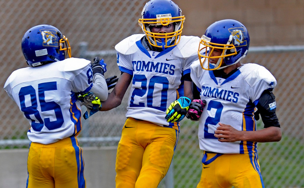 . Minneapolis Edison running back Perry Quindell, center, celebrates his first-half touchdown, one of three TDs he scored in the game, with teammates Walker Charles, left, and Felix-Twiet Deshaon against St. Paul Humboldt at the Bob Ryan Athletic Complex in St. Paul on Thursday, Aug. 28, 2014. Edison beat the Hawks 40-7.  (Special to the Pioneer Press: A.J. Olmscheid)