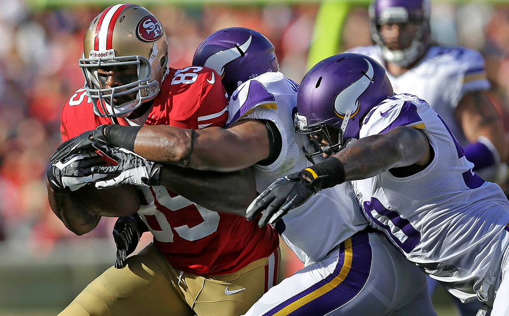 . 49ers tight end Vernon Davis, left, is tackled by Vikings defensive back Jamarca Sanford, center and linebacker Erin Henderson during the first quarter. (AP Photo/Marcio Jose Sanchez)