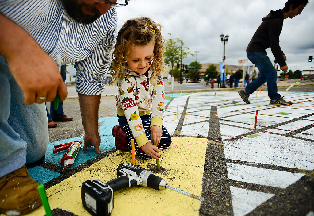 """. Three-year-old Evelyn Pennington of St. Paul puts a small rod in a hole in a street map of her favorite part of St. Paul -- the Children\'s Museum. With the help of James Wheeler, left, Pennington and her mother Jennifer (not pictured) drilled the hole and tied a string to the rod to measure biking time as part of an art piece titled \""""Mapping the Ave.\"""" (Pioneer Press: Ben Garvin)"""